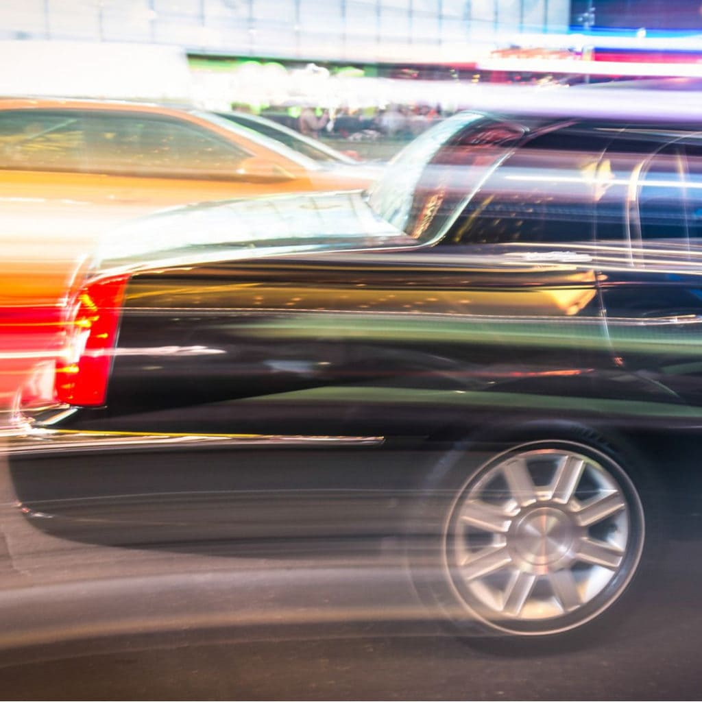 Limousine speeding through a city.