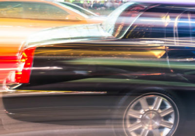 Limousine speeding through a city.