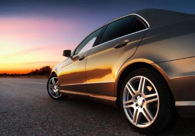 A chauffeured black car drives towards the horizon at sunset.